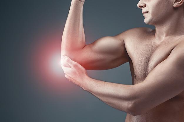 팔꿈치에 통증이 있는 남자. 회색 스튜디오 배경에 통증 완화 개념 프리미엄 사진