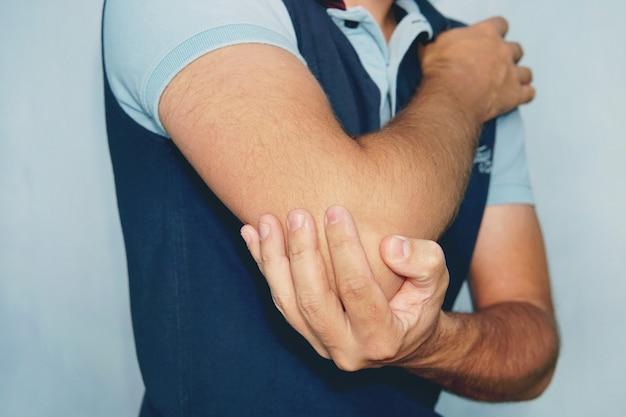 팔꿈치에 통증이 있는 남자. 통증 완화 개념입니다.