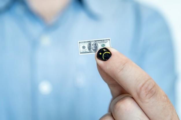 페인트 손톱을 가진 남자입니다. 남성 손톱의 디자인. 남자 매니큐어. 손을 잡고 미니어처 달러 메모입니다. 달러 인플레이션의 개념입니다. 직원의 작은 급여.