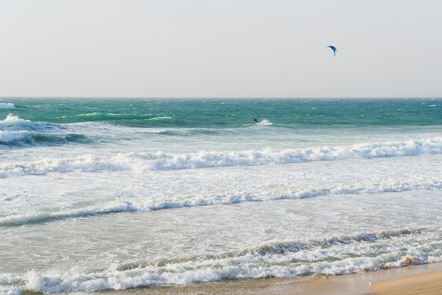 A man with parachute rides on a surfboard on large waves in the sea or ocean.