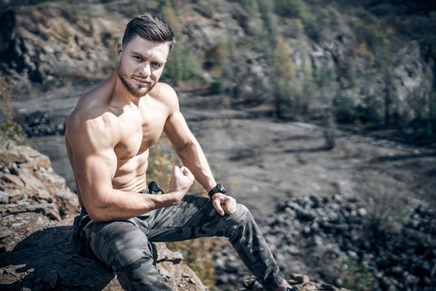 完璧な体で筋肉をポンピングする男。採石場に座っています。灰色の岩の背景。
