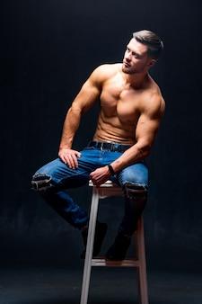 高い椅子に座っている完璧な体を持つ男。暗い背景。男性の美しさ。