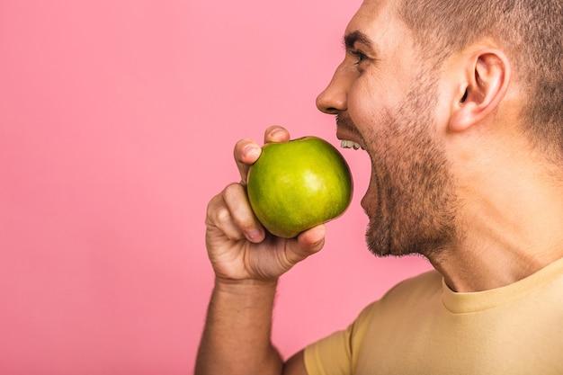 완벽한 하얀 치아와 녹색 사과를 가진 남자. 완벽한 치아와 미소를 보여줍니다.