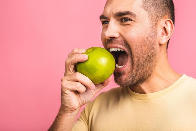完璧な白い歯と青リンゴを持つ男。完璧な歯と笑顔を見せています。