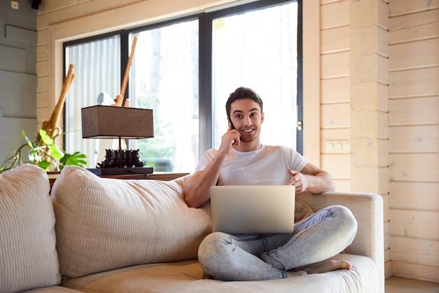 Человек с телефоном и ноутбуком дома