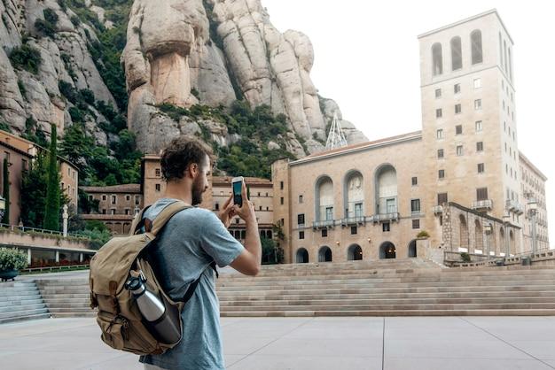 モンセラット修道院、バルセロナ、スペインでselfie写真を撮る携帯電話を持つ男