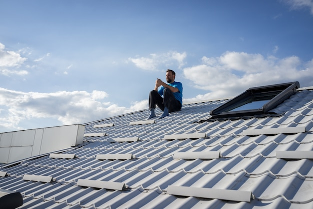 Man with phone on the top of house roof