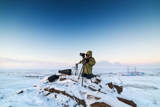 북극 툰드라에서 timelapse 사진을 찍는 삼각대에 사진 카메라를 가진 남자. 조명 상태가 좋지 않습니다.