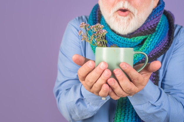 錠剤とお茶の治療薬を持つ男薬の丸薬を服用している老人ひげを生やした男