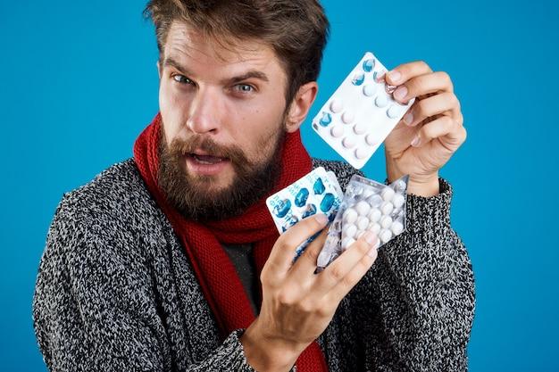 Человек с таблетками на синем лекарстве здоровья и теплой одежде.