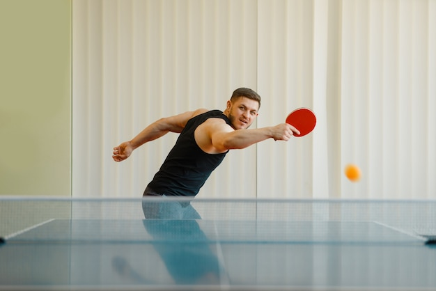 Man with ping pong racket plays the ball off