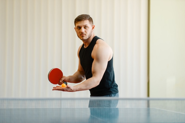 Man with ping pong racket preparing to hit a ball, workout indoors.