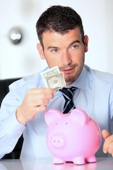 Человек с розовой копилкой и одной долларовой банкнотой