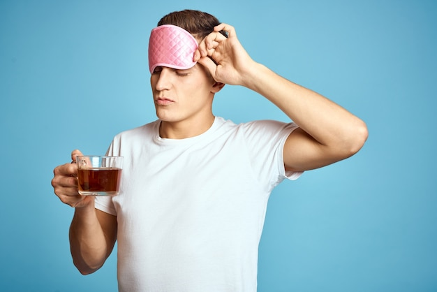 Man with pink sleep mask and cup of tea drink cheerfulness model breakfast
