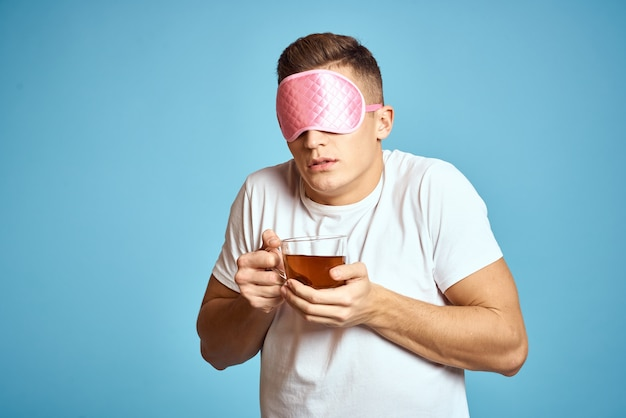 Man with pink sleep mask and cup of tea drink cheerfulness model breakfast.