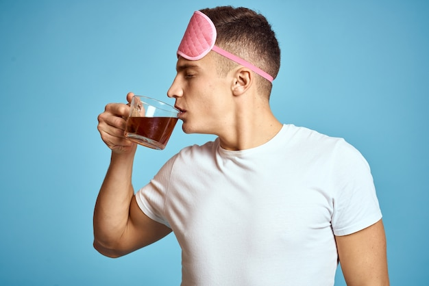 Man with pink sleep mask and cup of tea