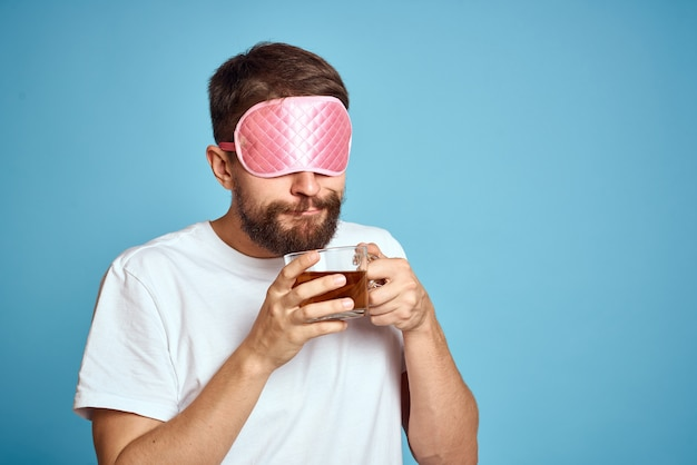 Man with pink sleep mask on his face and a cup of tea in his hands