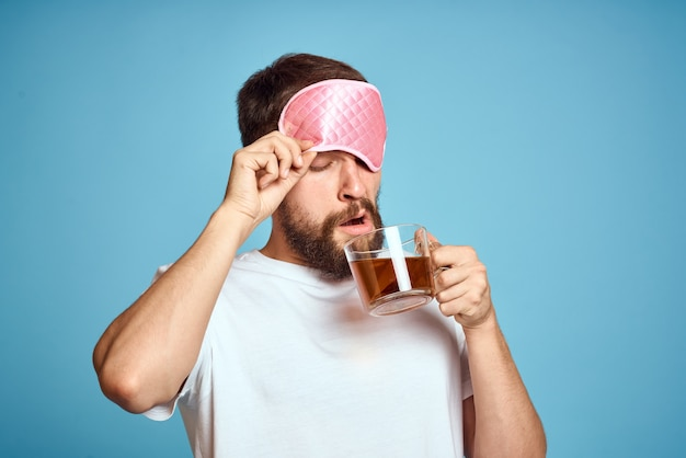 Man with pink sleep mask on his face and a cup of tea