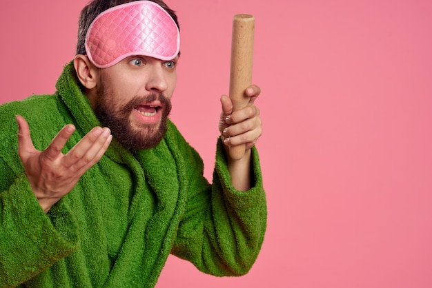 A man with a pink sleep mask on his face in a green robe with a rolling pin in his hand.