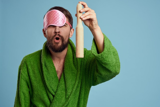 A man with a pink sleep mask holds a rolling pin in his hand and a green robe blue space emotions model.