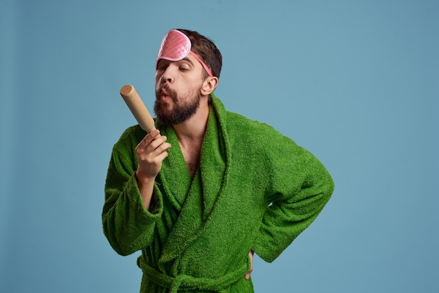 A man with a pink sleep mask holds a rolling pin in his hand and a green robe blue space emotions model