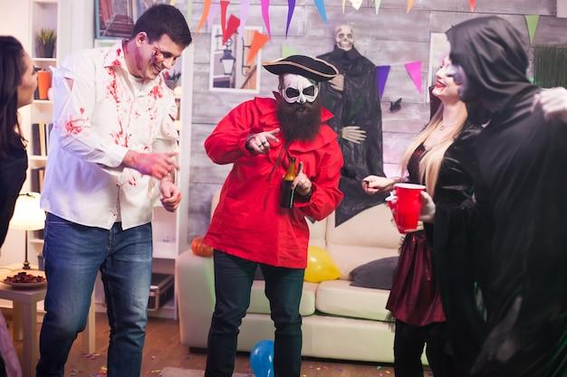 Uomo con costume da pirata che tiene una birra alla festa di halloween con i suoi amici.
