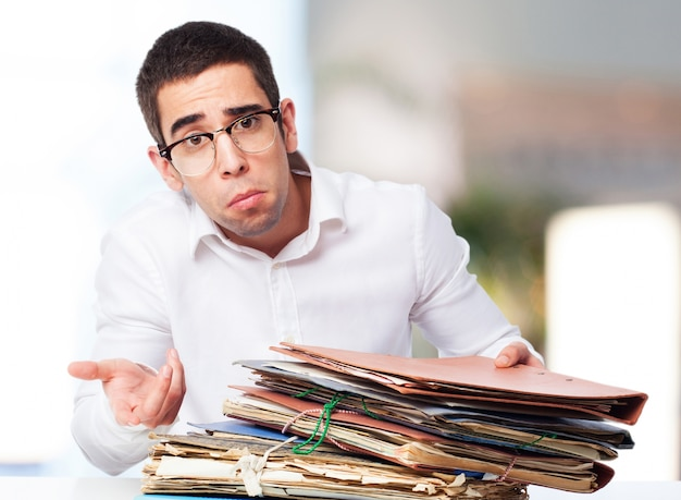 Man with pitying face with a mountain of folders