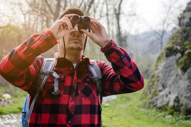 격자 무늬 셔츠와 쌍안경 야외를 가진 남자