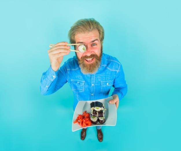 Мужчина с тарелкой суши и маринованным имбирем доставка суши японская еда маки роллы морепродукты