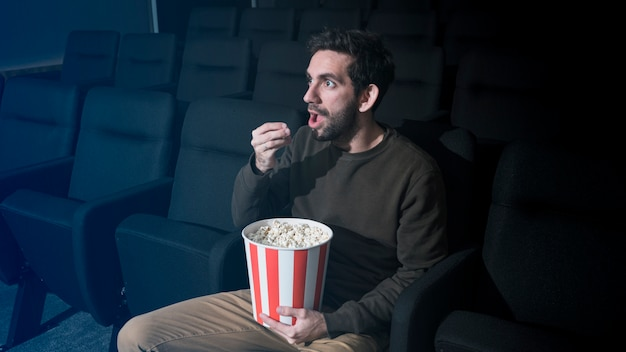 Man with popcorn in cinema