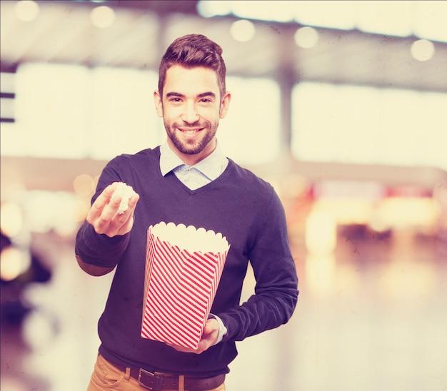 L'uomo con popcorn in una mano e un pacchetto in un altro