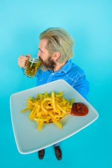 감자 튀김을 든 남자는 패스트 푸드 감자 튀김을 건배 맥주를 마시고 감자 튀김을 먹는 감자 남자
