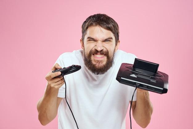 Человек с приставкой в руке джойстик игры образ жизни весело розовая белая футболка.