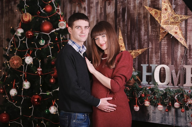 Man with a pregnant woman posing near the christmas tree