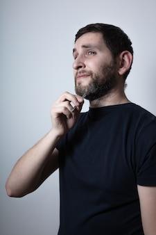Man with problem of graying beard plucking hair with tweezers from beard. macro shooting