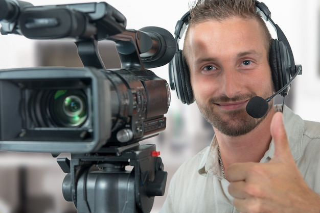 Man with professional camcorder and headphones
