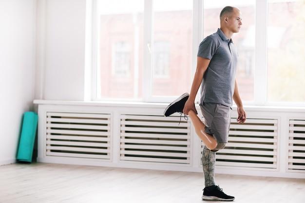 Человек с протезом ноги делает упражнения