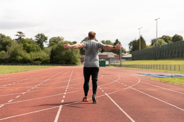 Man with prosthesis on running track full shot