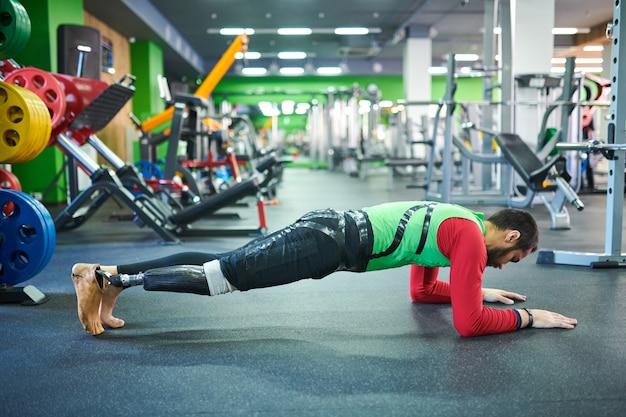 Человек с протезом ноги выполняет упражнения доски