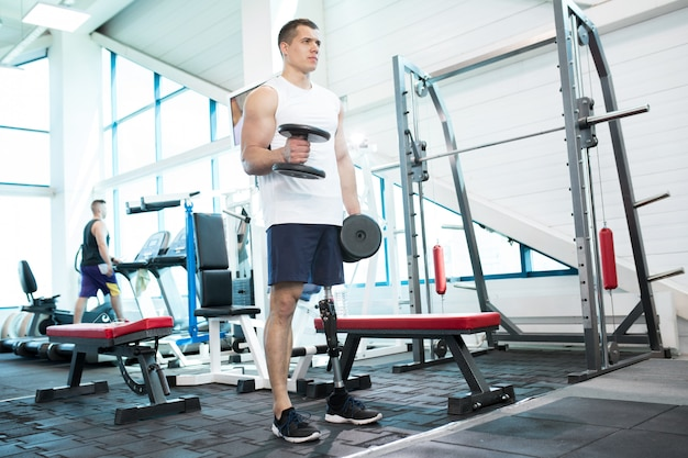 Man with prosthetic leg training in gym