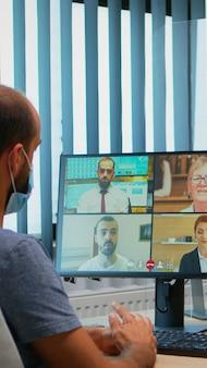 新しい通常のオフィスでのオンライングループビデオ会議に参加している保護マスクを持つ男。インターネット技術を使用して、仮想会議を持って話している職場のチャットで働いているフリーランサー