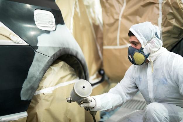 Человек с защитной одеждой и маской, рисующей автомобильный бампер в ремонтной мастерской