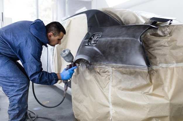 Man with protective clothes and mask painting car using spray compressor. selective focus.
