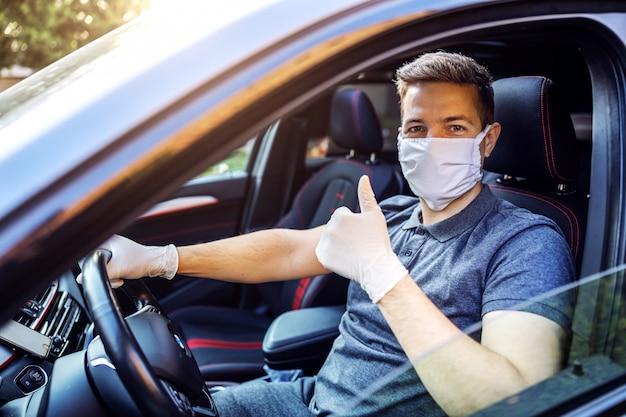 防護マスクと手袋をはめて車を運転する男。エピデミック。親指を立てて安全を確保します。