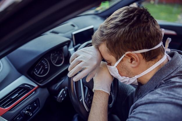 防護マスクと手袋で頭痛を持つ車を運転する男。エピデミック。おげんきで。