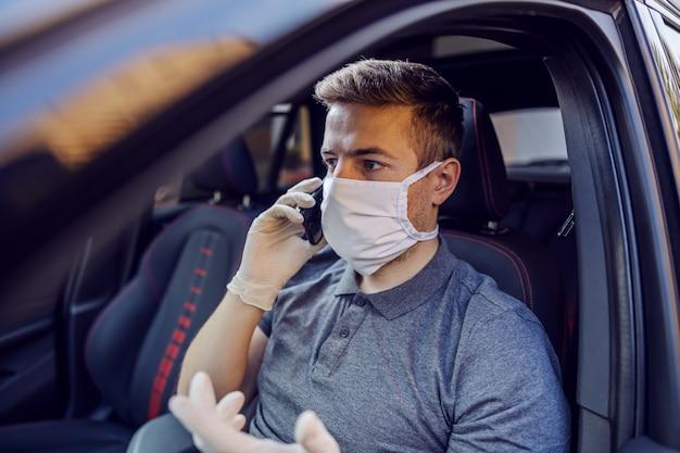 防護マスクと手袋の携帯電話のスマートフォンで話している車を運転する男。エピデミック。おげんきで。