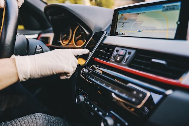 防護マスクと手袋を携帯電話のスマートフォンで入力して車を運転する男。エピデミック。おげんきで。