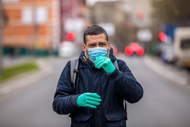 Man with a protective mask on his face is standing on the street