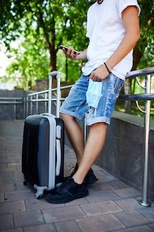 手に保護マスクを持った男、スーツケースと携帯電話を持って屋外の公園に立って、コロナウイルスパンデミック中の生活、空の旅、旅行のコンセプト。