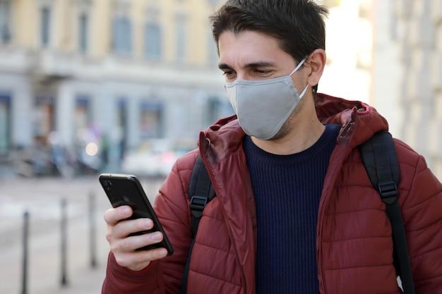 保護マスクを持った男が通りで彼のスマートフォンを見る